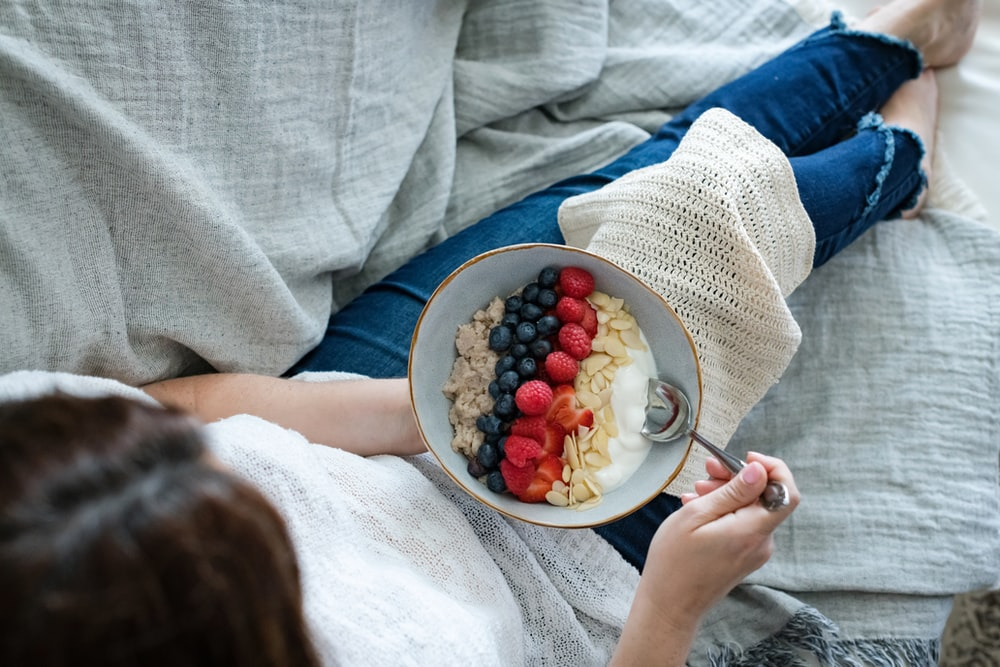 person holding white ceramic bowl with red and blue berries
