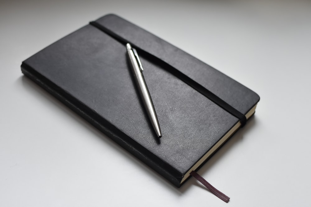 silver click pen on black book