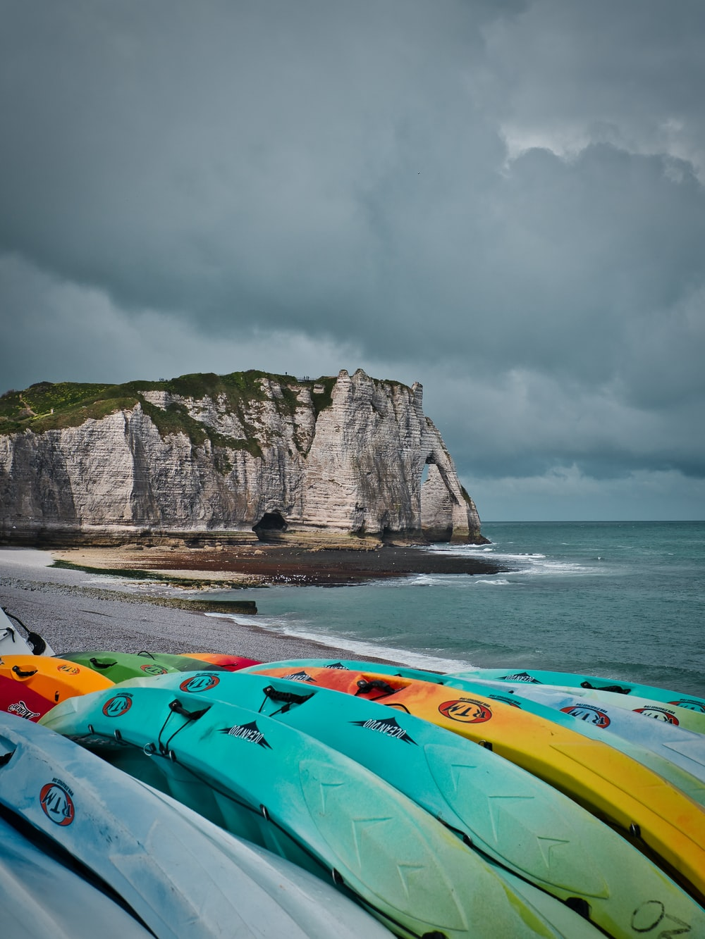green and yellow kayak on sea shore near mountain under cloudy sky during daytime