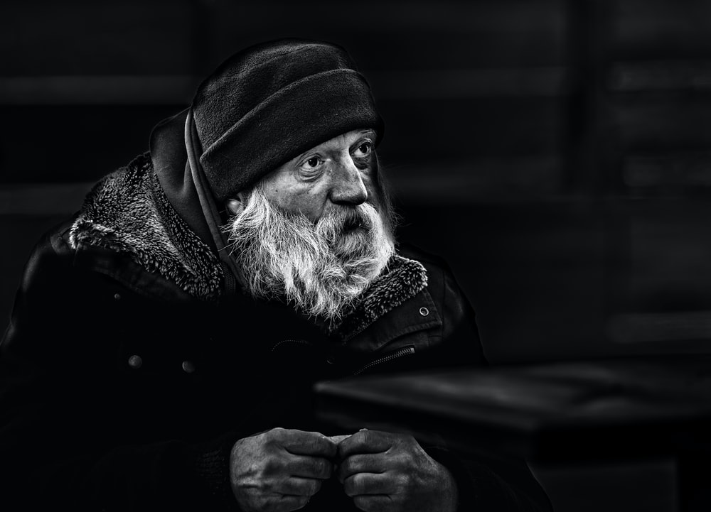 grayscale photo of man wearing black and white scarf