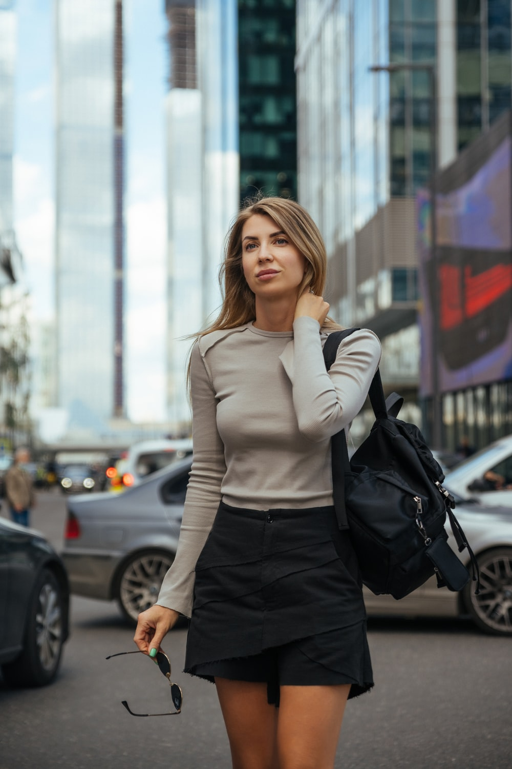 woman in white long sleeve shirt and black skirt standing on sidewalk during daytime
