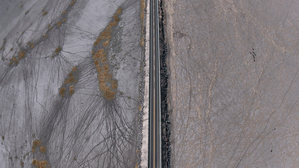 aerial view of road between snow covered ground