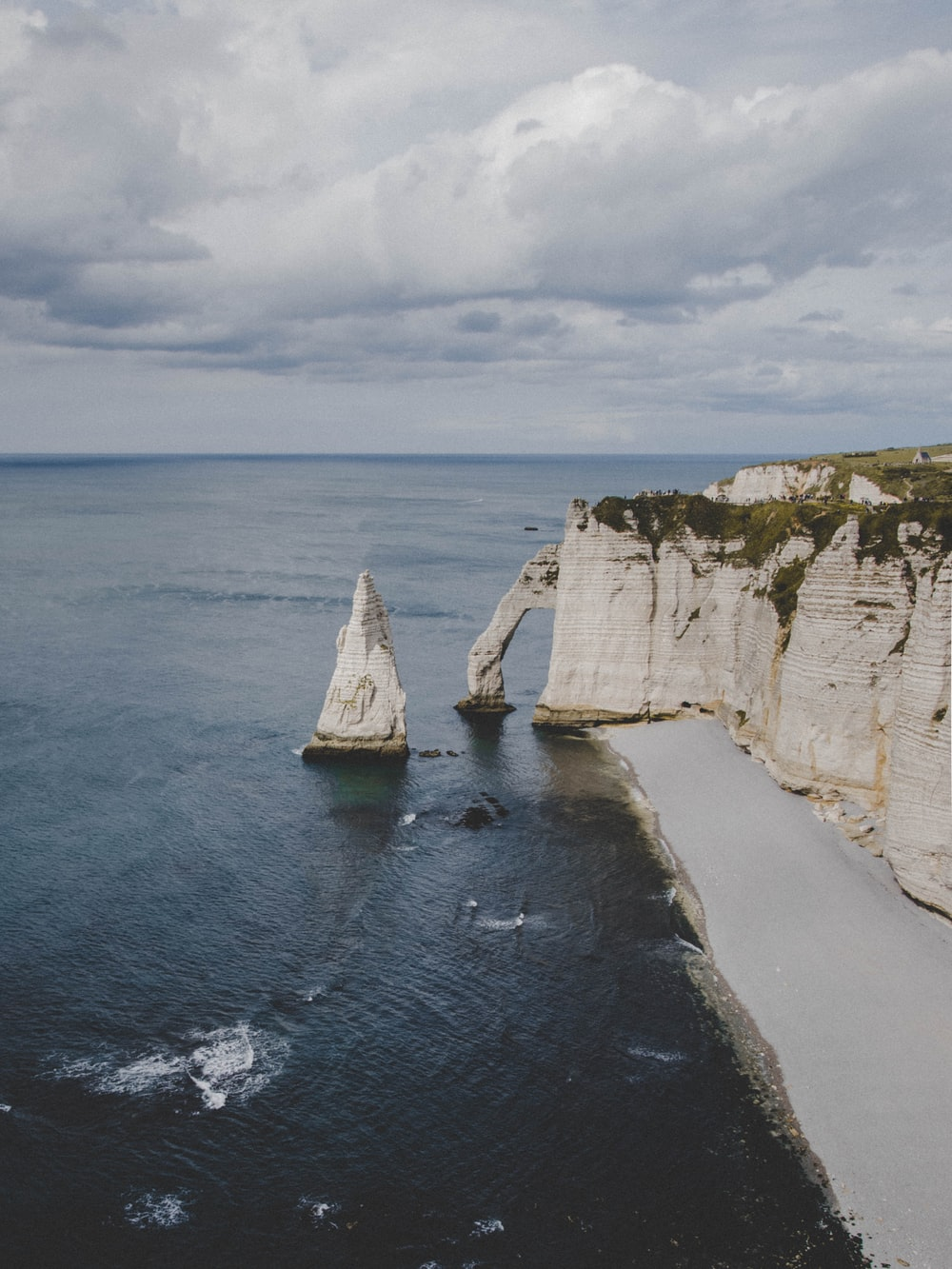 white rock formation on sea under white clouds during daytime