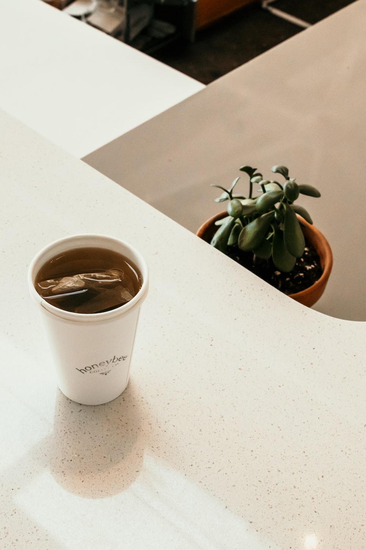 white ceramic mug with coffee on white table