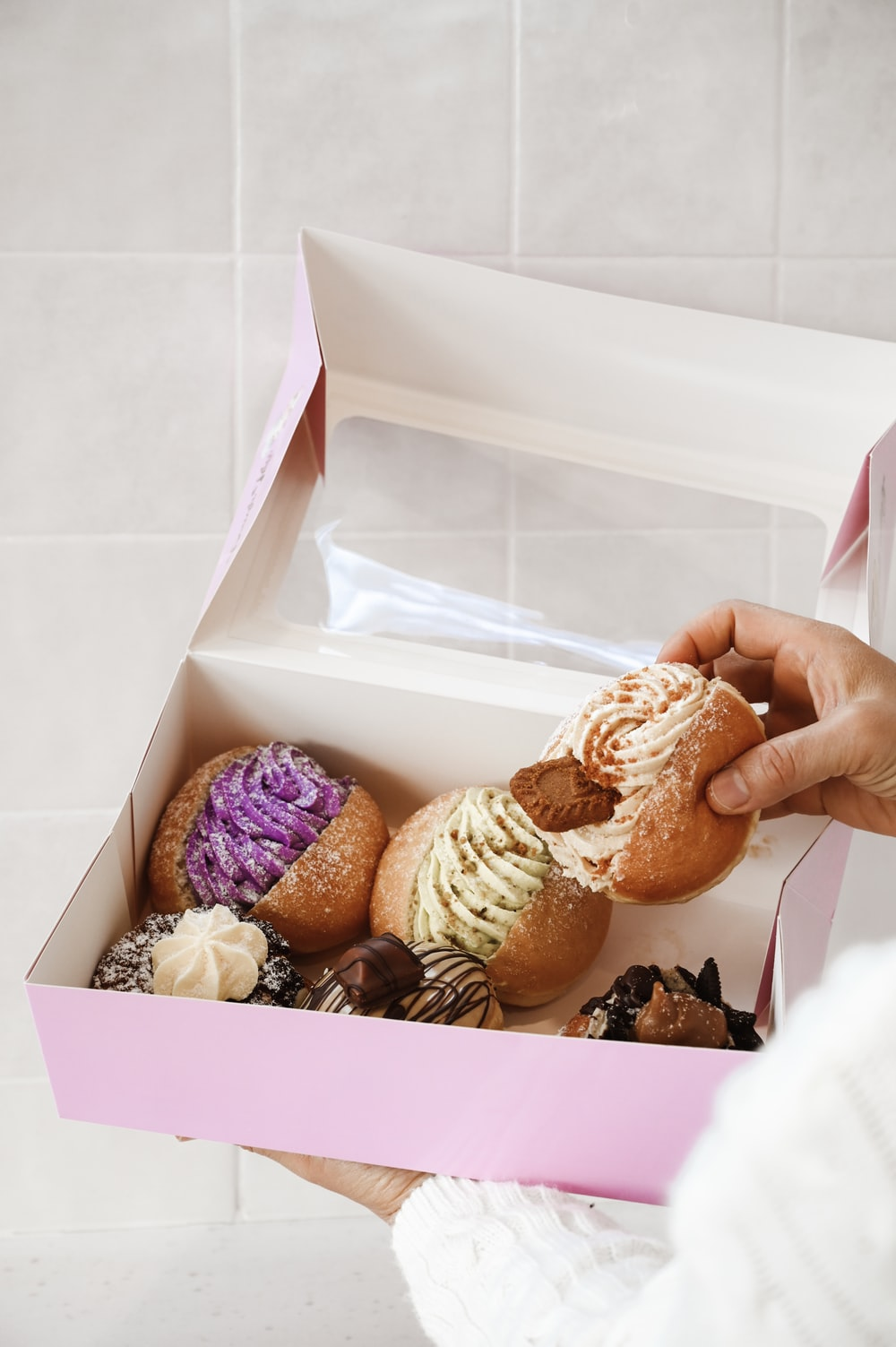 person holding box of doughnuts
