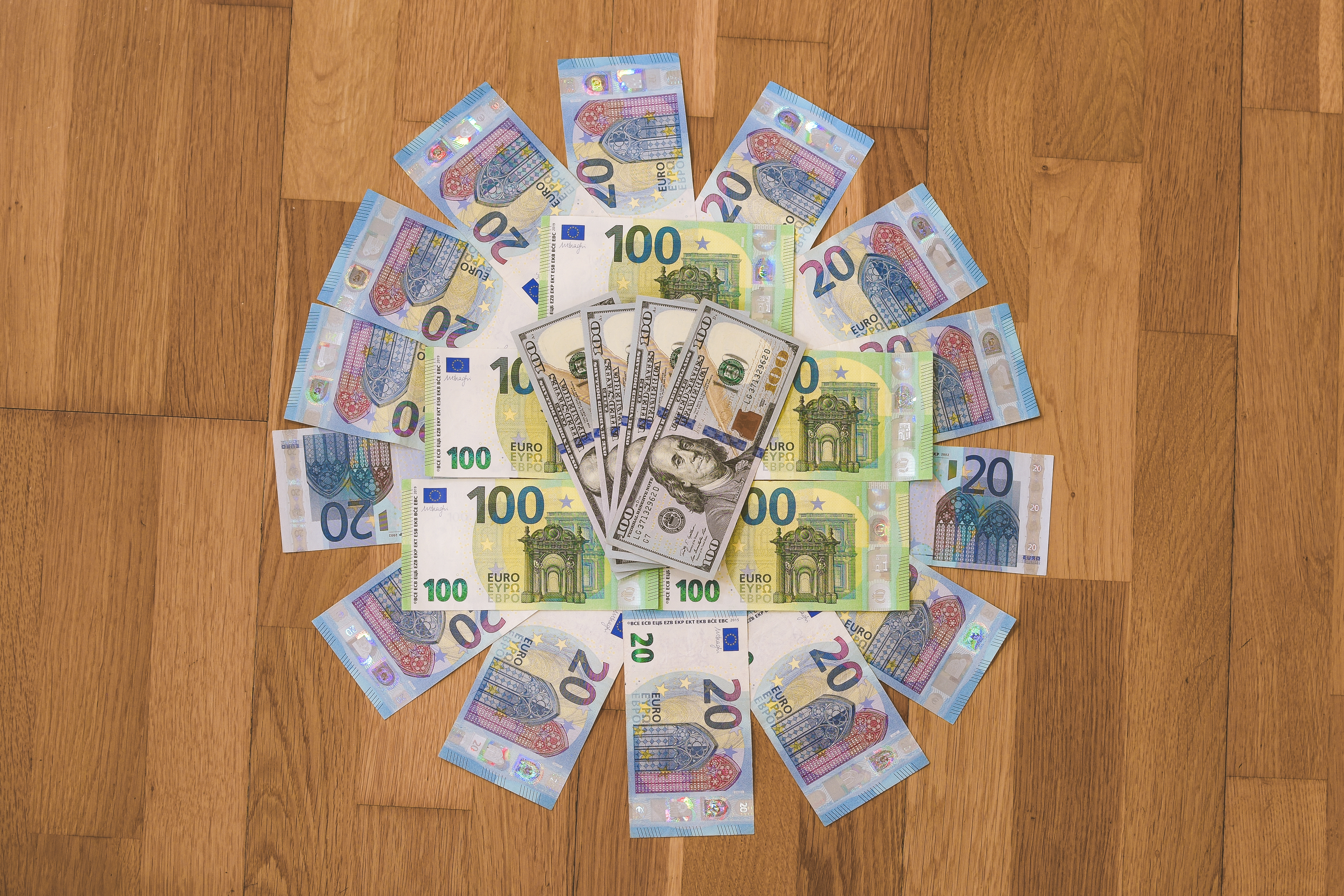 20, 100 Euro (EUR), and 100 Dollar (USD) banknotes placed on a wooden surface in a circular shape.