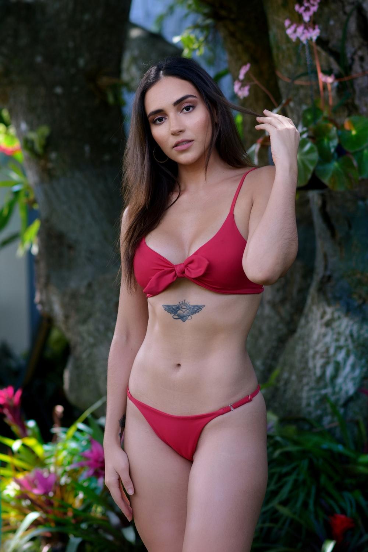 woman in red bikini standing near green plant