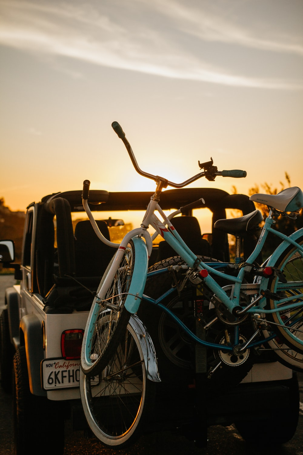 blue city bike parked beside white car during sunset