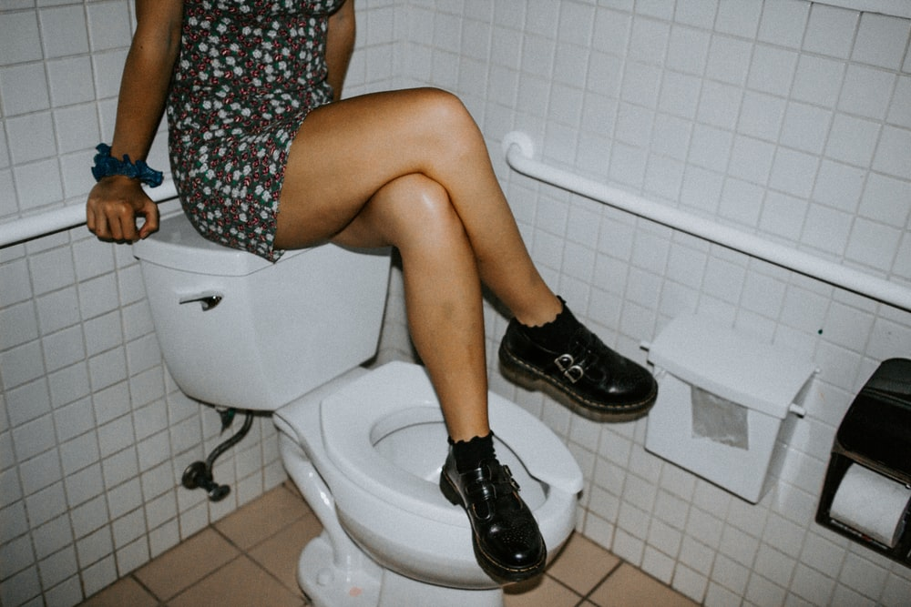 woman in black and white floral dress sitting on white ceramic toilet bowl
