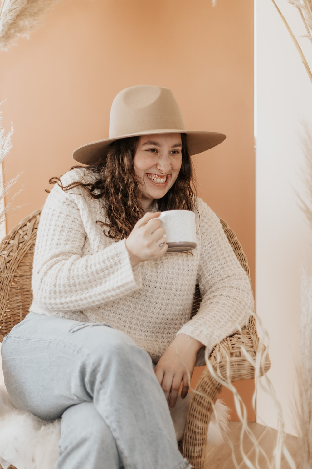 woman in white knit sweater and gray pants holding white ceramic mug