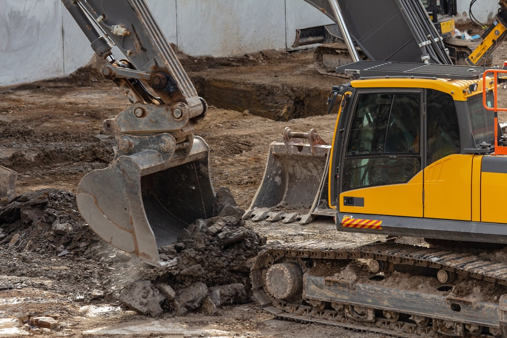 yellow and black excavator on brown soil