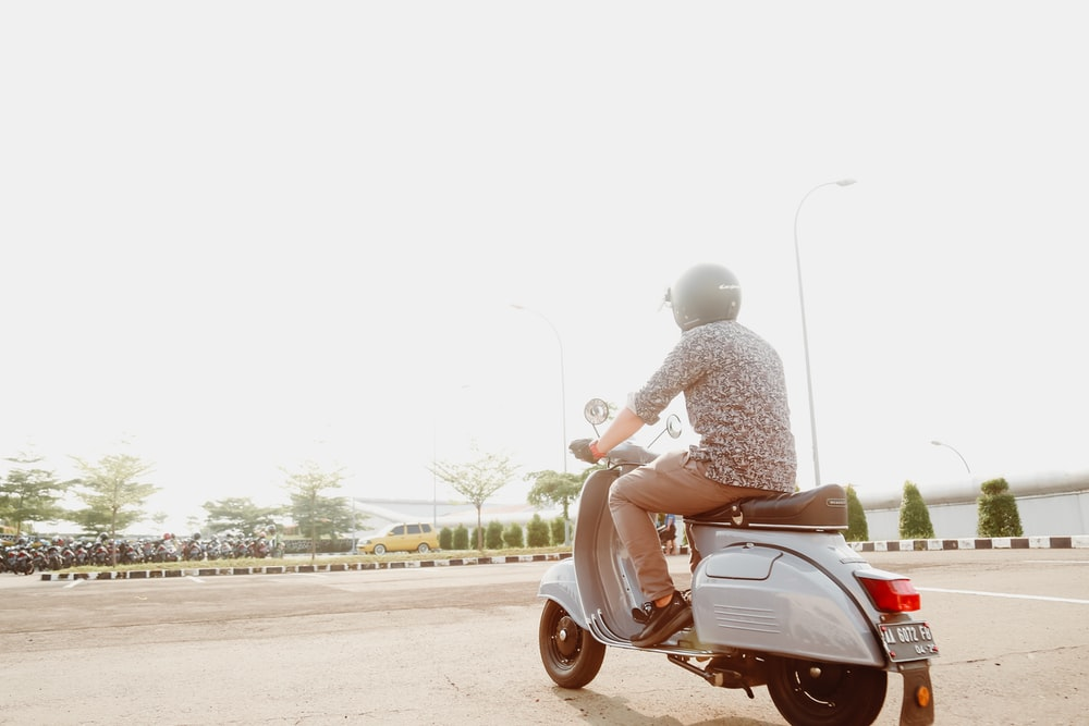 man in gray jacket riding red motor scooter on road during daytime