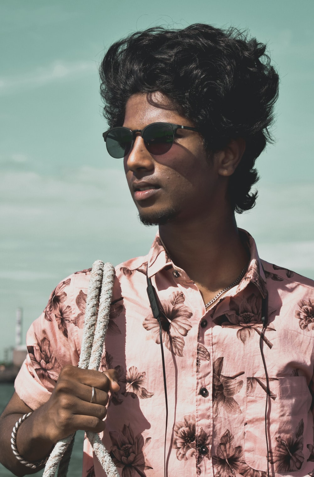 man in pink and white floral button up shirt wearing black sunglasses