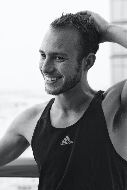 man in black tank top smiling