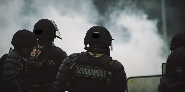 2 men in black police uniform standing on road during daytime