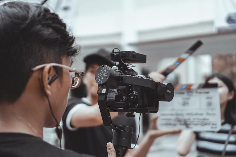 man in black framed eyeglasses holding black video camera
