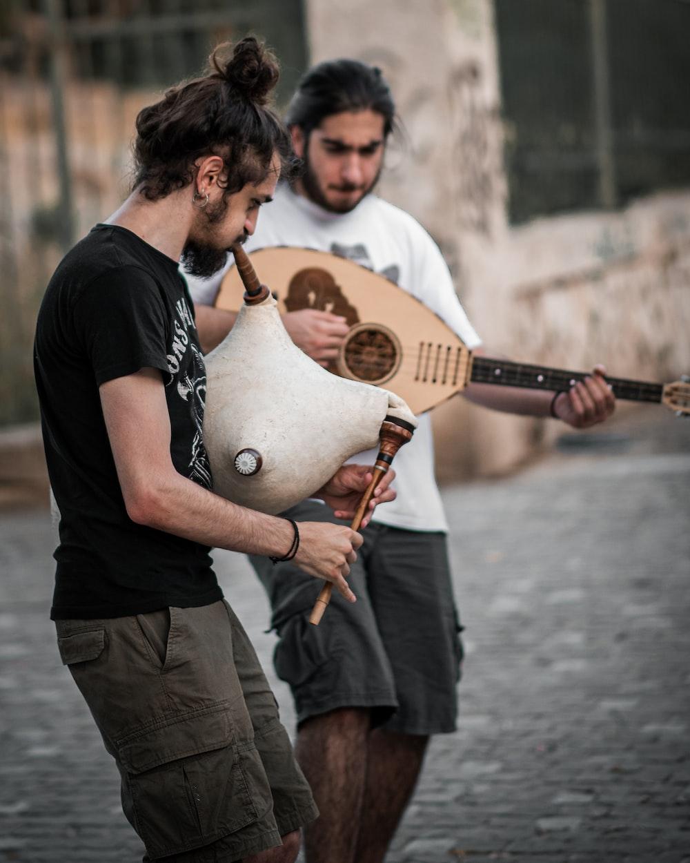 man in black t-shirt playing acoustic guitar