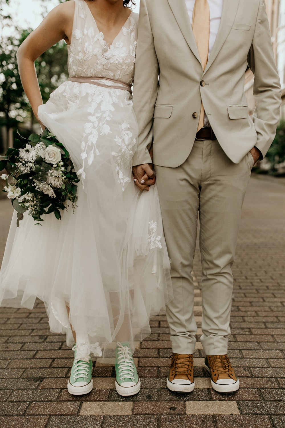 man in gray suit jacket and woman in white wedding dress holding bouquet of white flowers