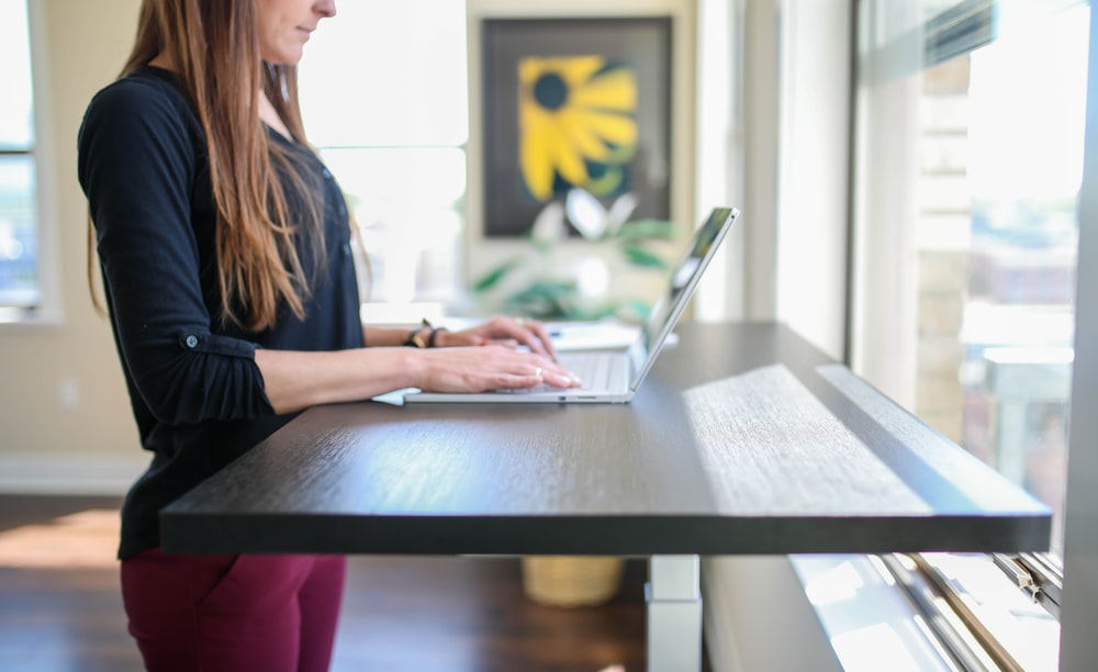 woman in black shirt sitting at the table using macbook