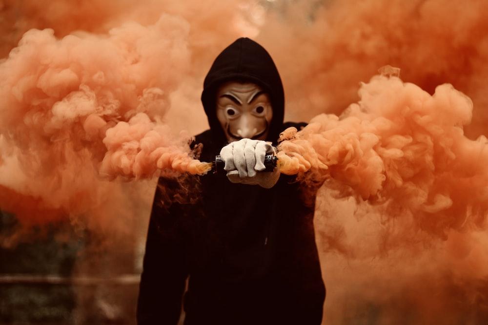 girl in black hoodie holding orange smoke