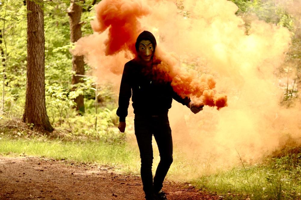 woman in black long sleeve shirt holding orange smoke