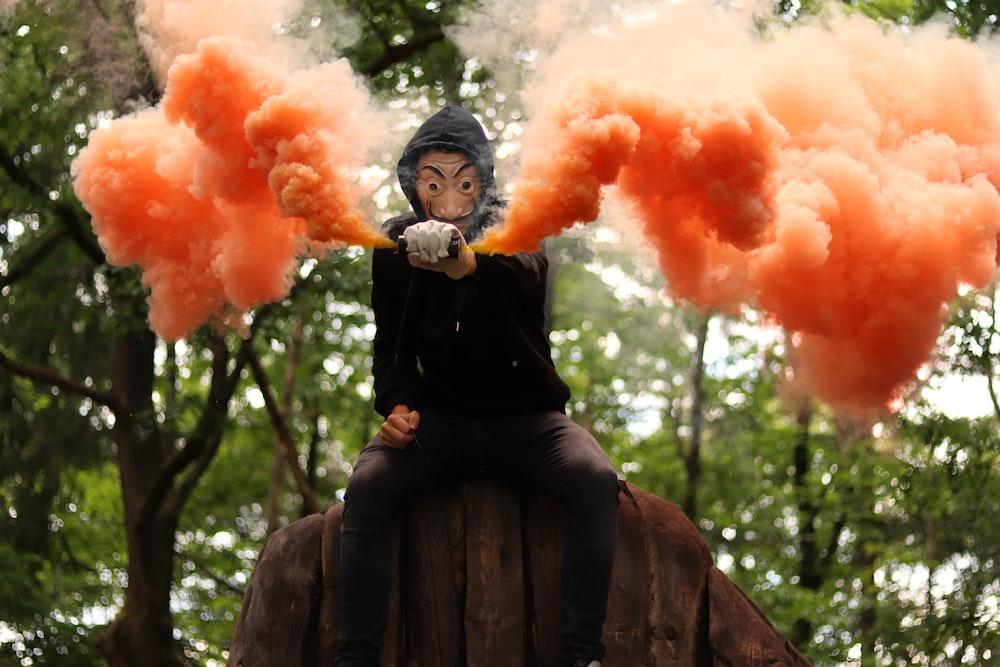 woman in black long sleeve dress holding orange smoke