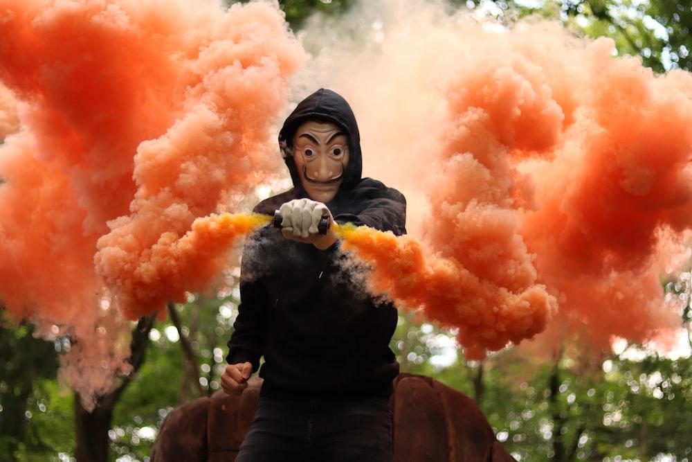 woman in black jacket holding orange smoke