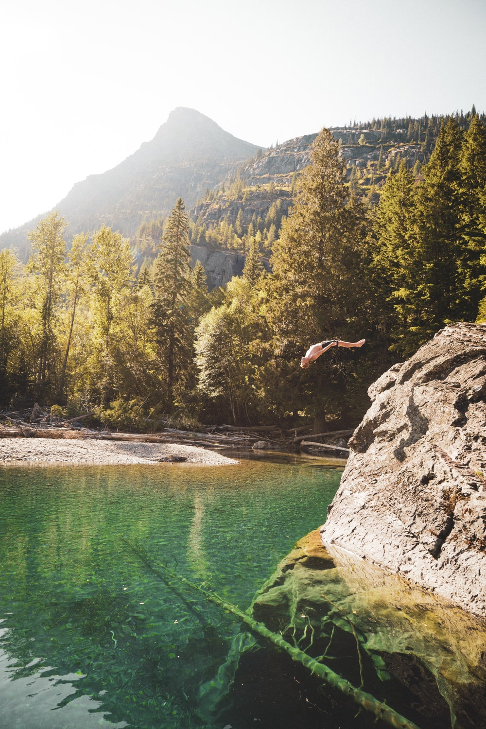 person jumping on water near green trees and mountain during daytime