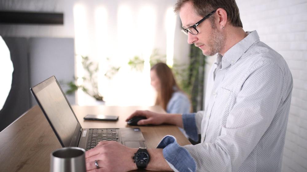 man in blue dress shirt using computer