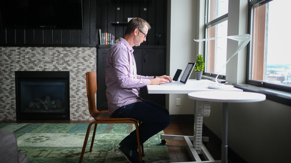 man in gray dress shirt sitting on brown wooden chair using macbook pro