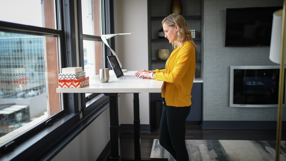 woman in yellow long sleeve shirt and black pants standing beside white table