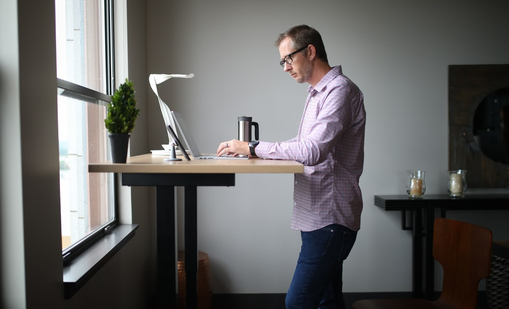 man in pink dress shirt and blue denim jeans standing beside brown wooden table