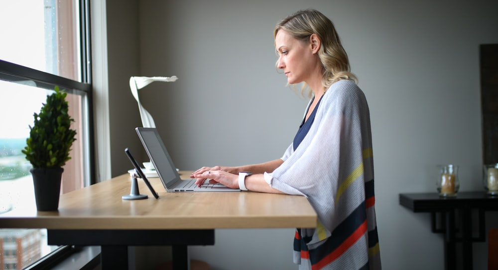 woman in white robe sitting on chair using laptop computer