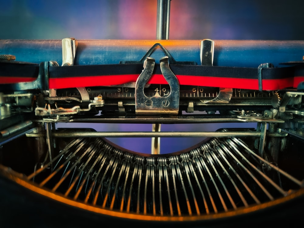 red and black typewriter on brown wooden table