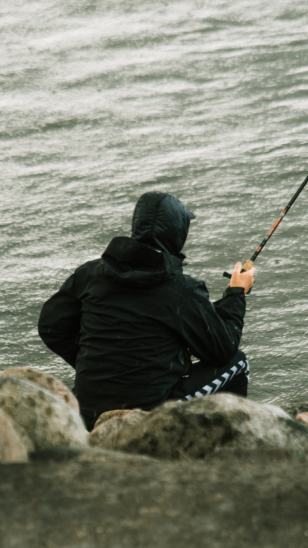 person in black jacket fishing on sea during daytime