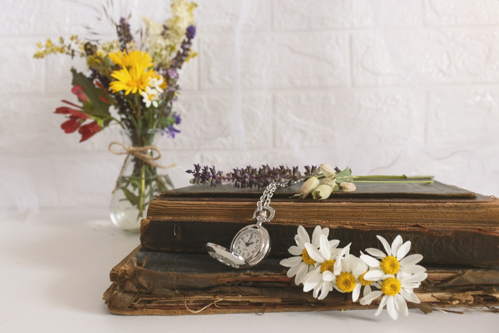 white and yellow flowers on brown wooden table