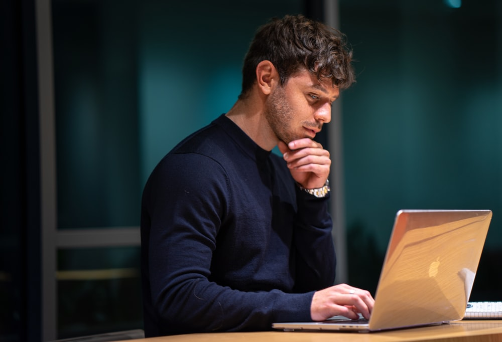 man in black long sleeve shirt sitting in front of macbook