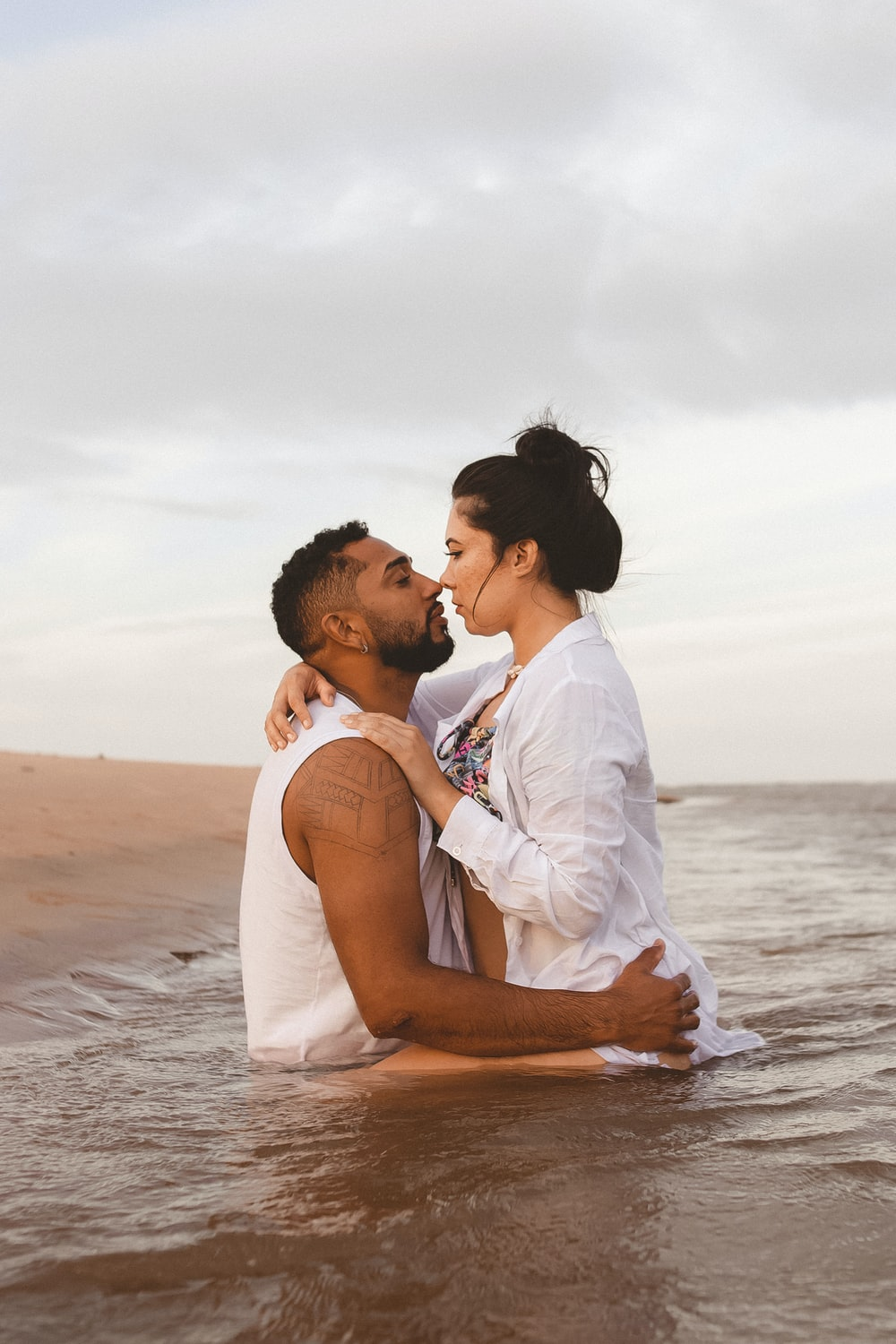 man in white dress shirt kissing woman in white dress on beach during daytime