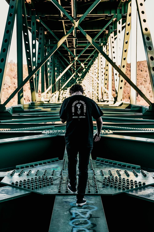 man in black jacket and blue denim jeans standing on bridge