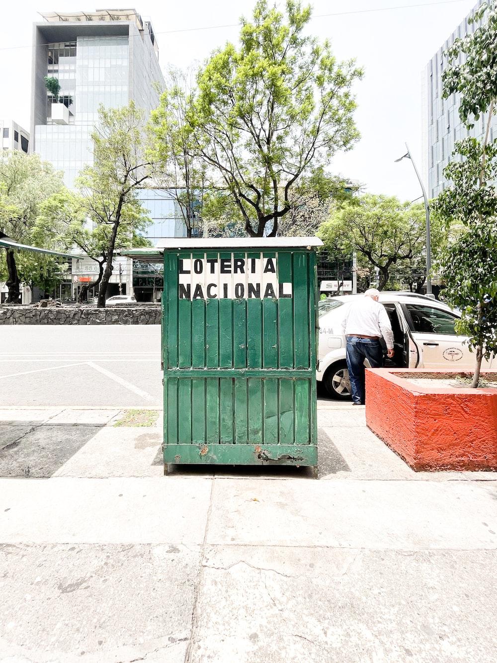 green trash bin near white car during daytime