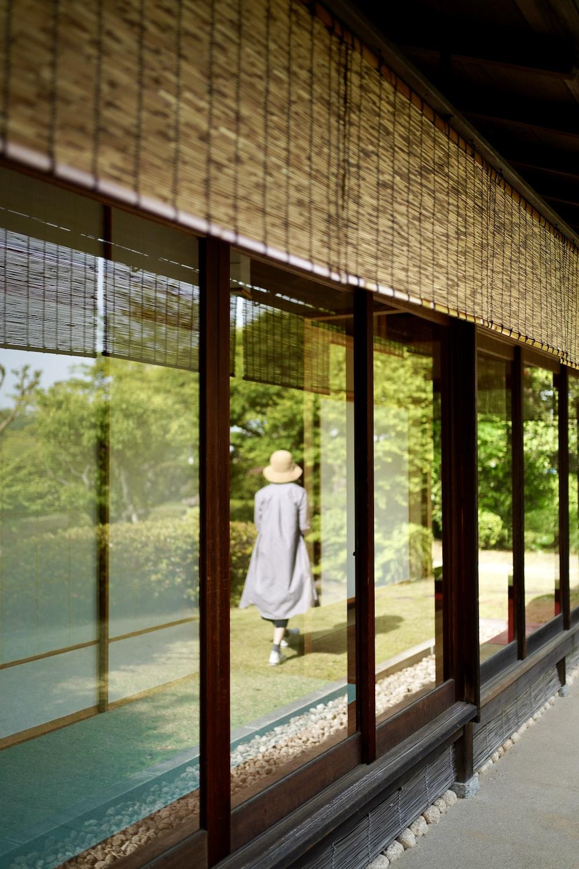 woman in white dress standing near glass window