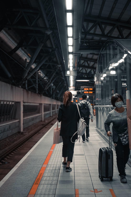 woman in black jacket walking on train station
