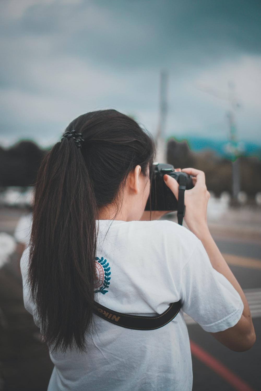 woman in white shirt using black dslr camera during daytime