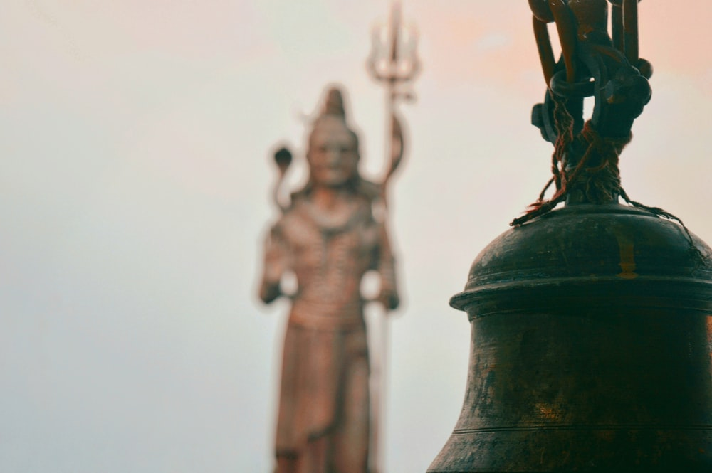black bell with three human statues