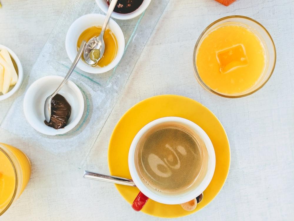 white ceramic mug with coffee on yellow saucer