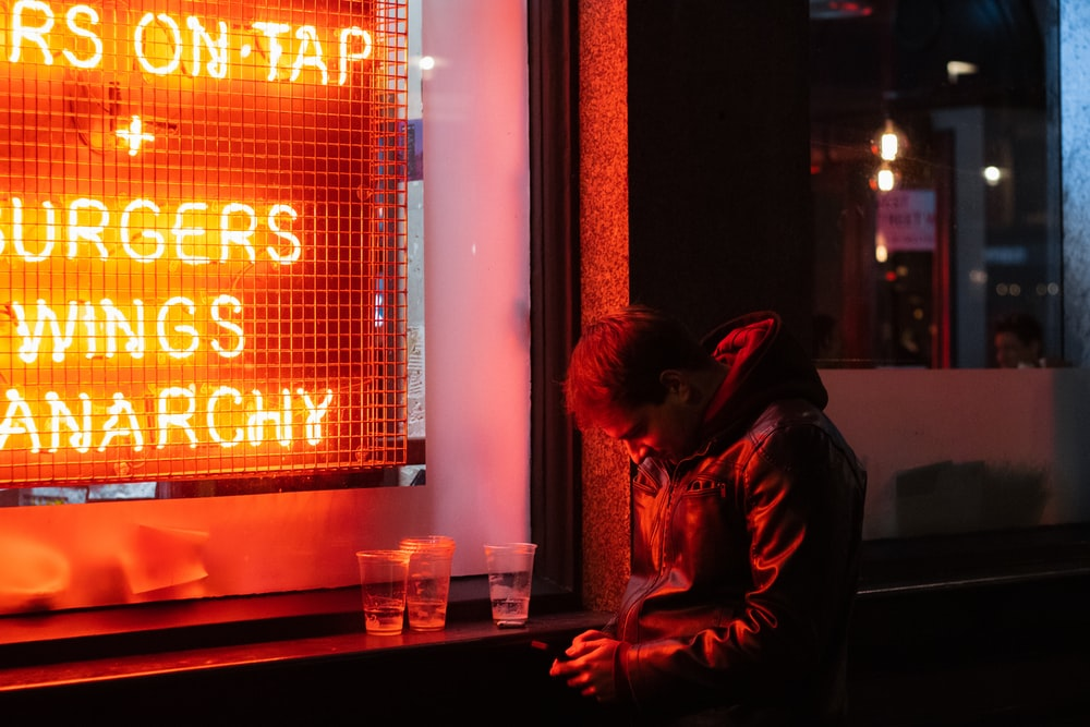 man in black leather jacket sitting beside red and black neon signage