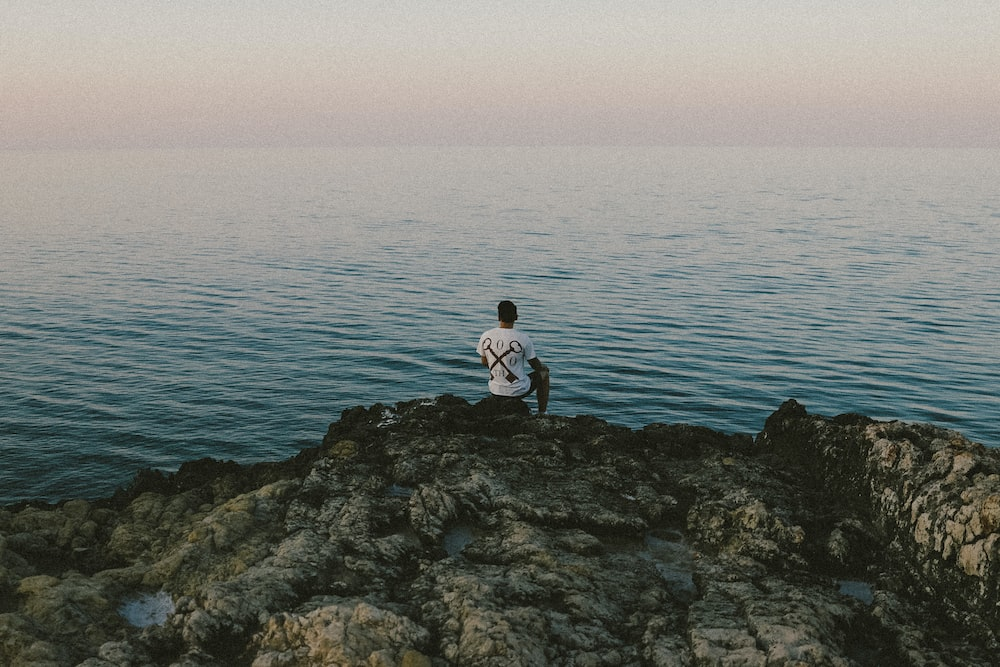 man in white shirt sitting on rock by the sea during daytime