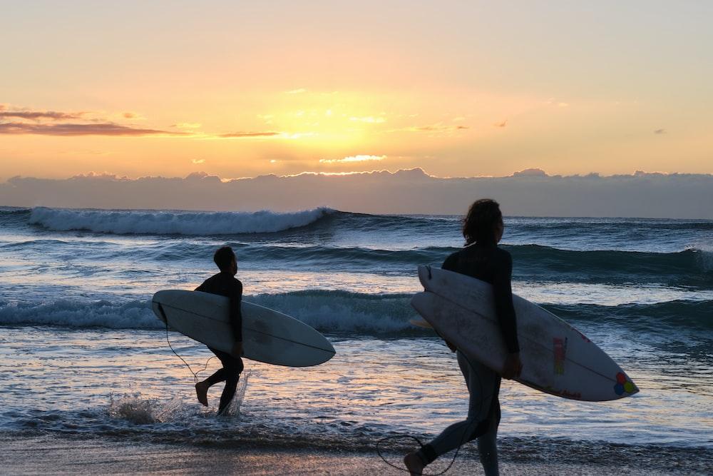 man holding white surfboard walking on beach during sunset