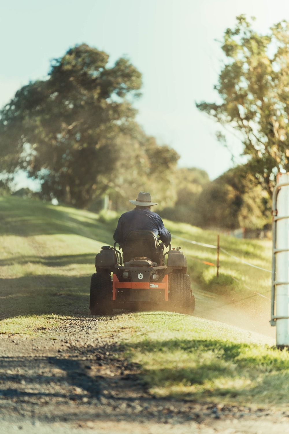 man riding red and black ride on lawn mower on green grass field during daytime