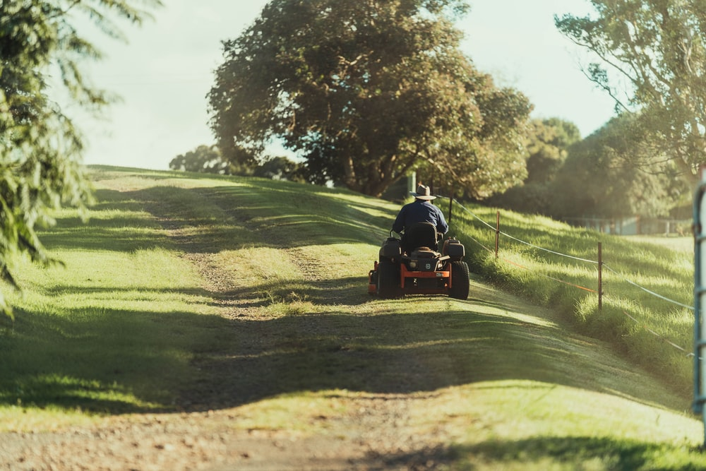 man riding on red atv on green grass field during daytime
